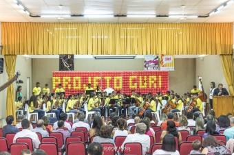 Criança tocam de camiseta amarela de frente para a platéia