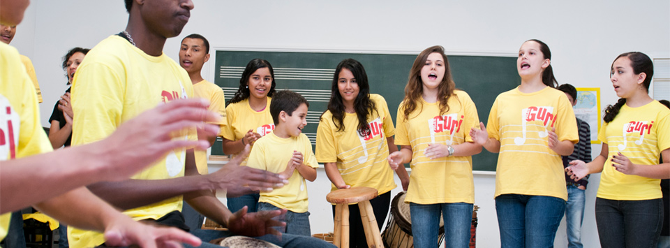 Children sitting in orchestra format being governed by a conductor