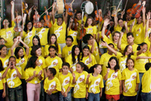 many children together, smiling and putting her hands and instruments up