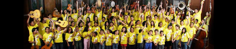 Imagem de alunos do Projeto Guri em momento descontraído, alegre e levantando seus instrumentos musicais para foto