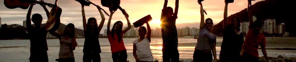 Foto de alunos do Grupo de Referência do Projeto Guride Santos na praia levantando seus instrumentos