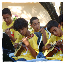 "picture of four young people dressing a yellow t-shirt of Guri, playing ""cavaquinho"", or chip"