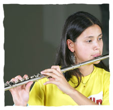 picture of a young girl dressing a yellow t-shirt of Guri, playing a flute