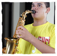 picture of a young boy dressing a yellow t-shirt of Guri, playing a saxophone
