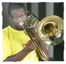 picture of a young boy dressing a yellow t-shirt of Guri, playing a trombone