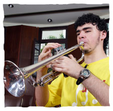 picture of a young boy dressing a yellow t-shirt of Guri, playing a trumpet