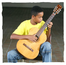 picture of a young boy dressing a yellow t-shirt of Guri, playing a guitar
