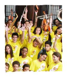 Foto de diversos alunos do Projeto Guri e seus instrumentos musicais