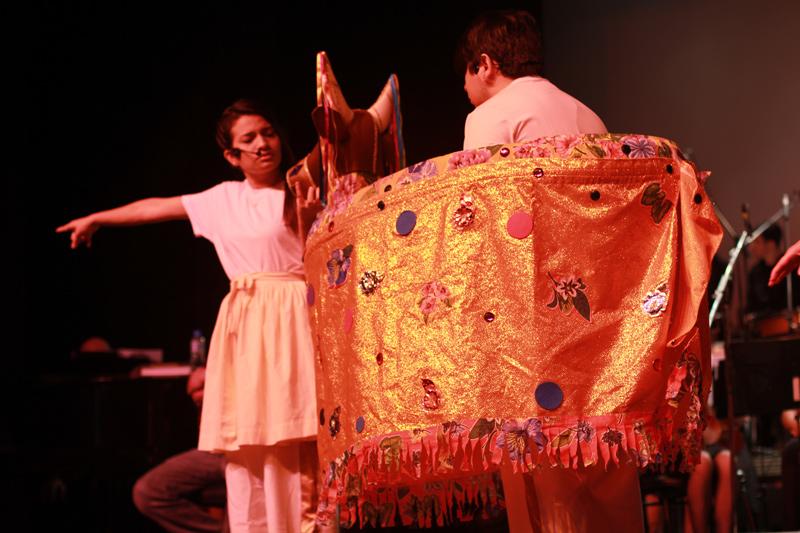 Imagem dos alunos apresentando o espetáculos e um menino vestindo o figurino que representa o Boi Bumbá