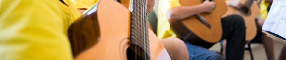 Foto de alunos tocando violão