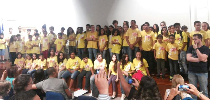 Crianças e jovens de camiseta amarela com o logo do Guri em vermelho fazem foto no festival Crie Sua Própria Música